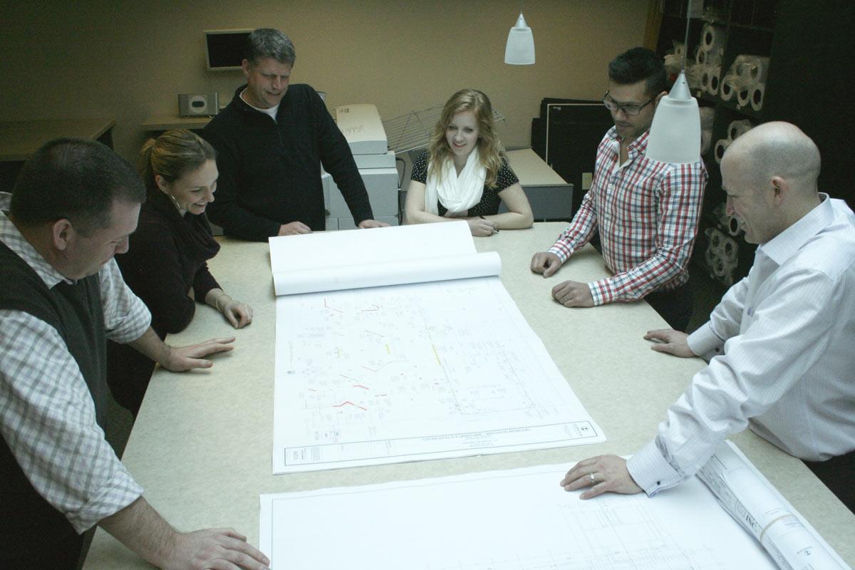 Tukka team looking at blueprint